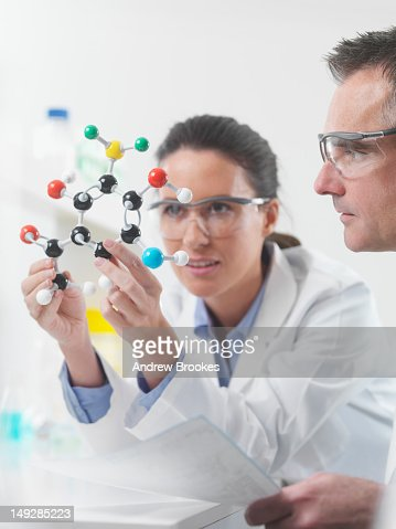 Scientists examining molecular model : Stock Photo