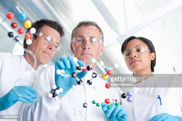 Scientists examining molecular models in lab