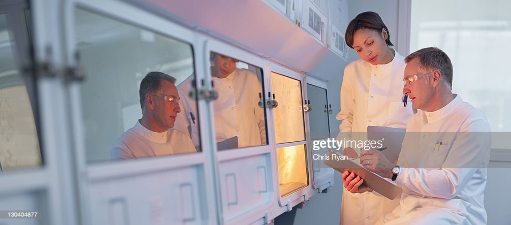 Scientists examining oven in lab : Stock Photo