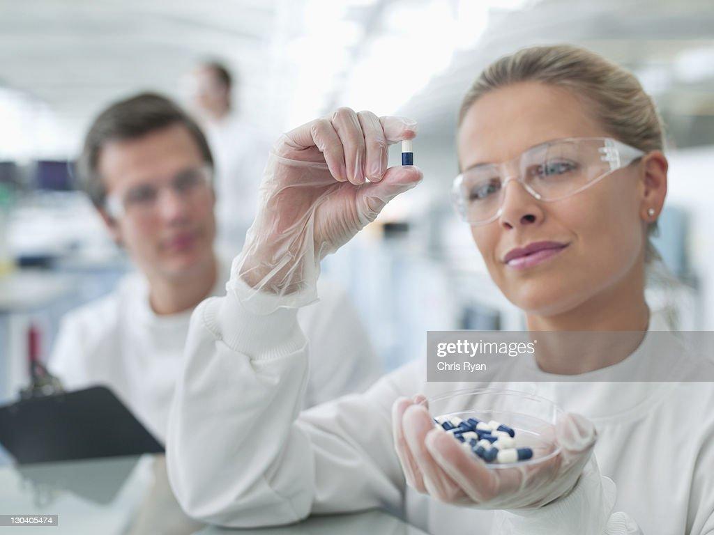 Scientists examining pills in lab : Stock Photo