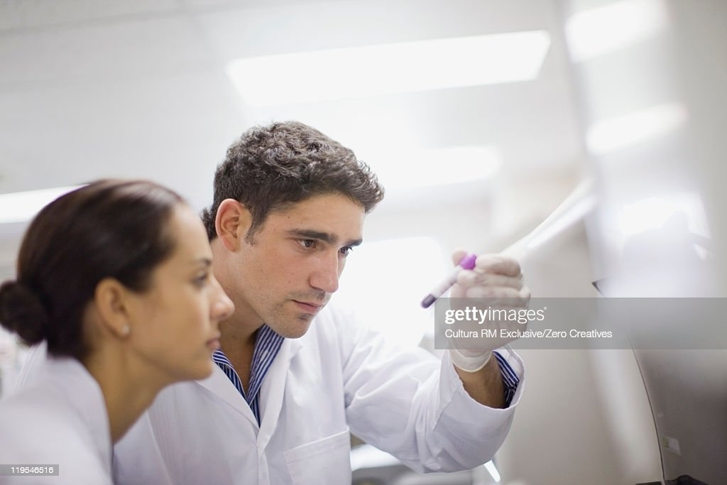 Scientists examining test tube in lab : Stock Photo