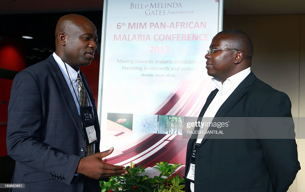 Scientists Halidou Tinto (L), Principal Investigator from the Nanoro, Burkina Faso trial and chairman of the Clinical Trials Partnership Committee (CPTC) overseeing the RTS,S malaria vaccine Phase III programme talks with fellow scientist and Investigator Lucas Otieno (R) during the 6th MIM Pan-African Malaria Conference held at the International Convention Centre in Durban on October 8, 2013. The theme of the conference is 'Moving Towards Malaria Elimination: Investing in Research And Control'. The conference ends on October 11, 2013.
