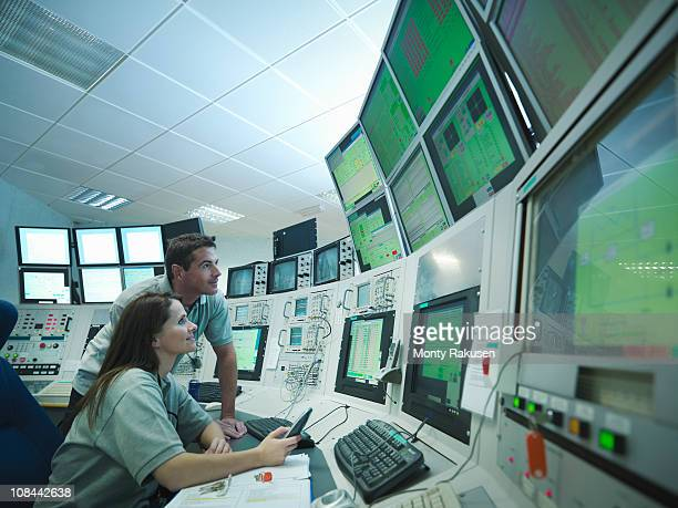 Scientists in particle accelerator control room, looking at monitors