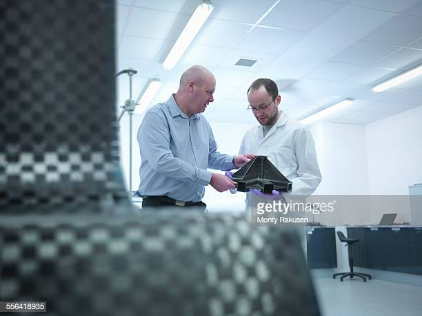 Scientists inspect carbon fibre part in carbon fibre laboratory