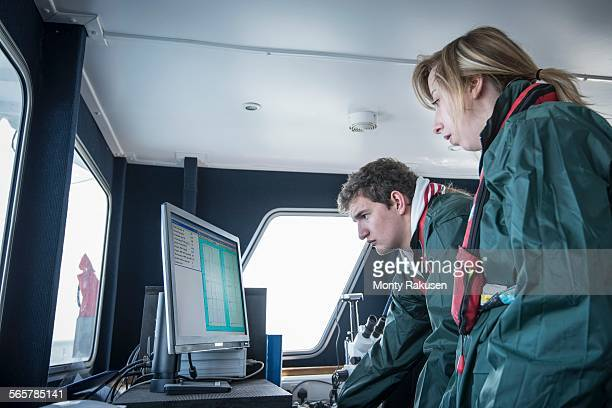 Scientists inspecting data on research ship