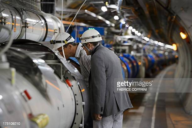 Scientists look at a section of the European Organisation for Nuclear Research Large Hadron Collider during maintenance works on July 19 2013 in...