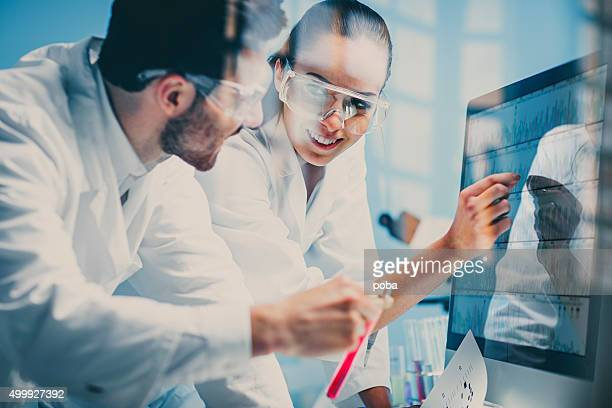 scientists looking at a DNA sequence on the monitor