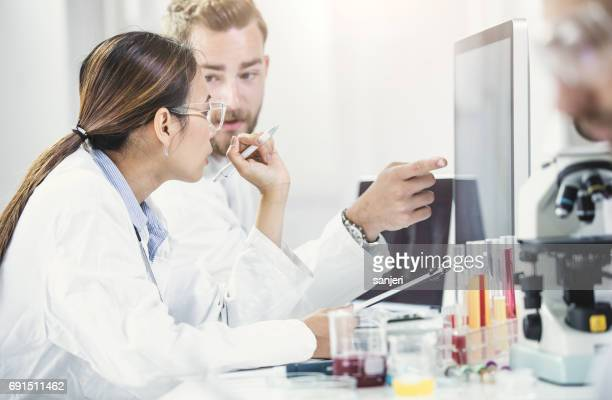 Scientists Looking at Computer Monitor and Discussing