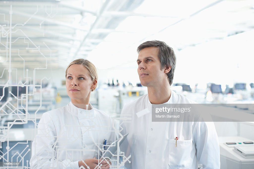 Scientists looking touch screen in lab : Stock Photo