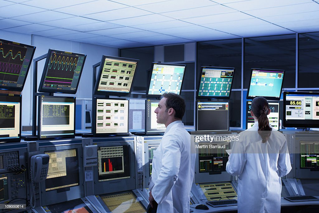 Scientists monitoring computers in control room : Stock Photo