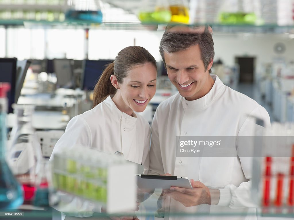 Scientists reading clipboard in lab : Stock Photo