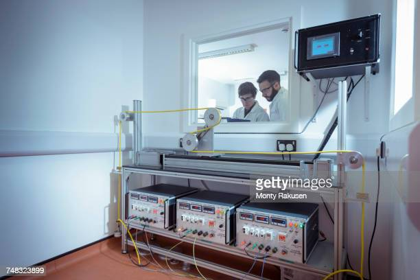 Scientists using cable bending test equipment to test electrical cable in electrical cable laboratory