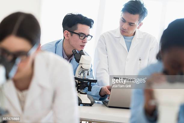 Scientists using microscopes and laptop in research laboratory