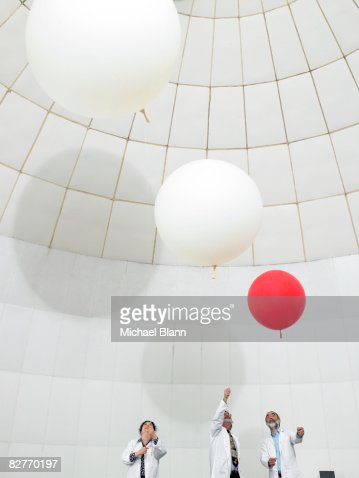scientists watch weather ballons float upwards : Stock Photo