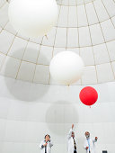 scientists watch weather ballons float upwards