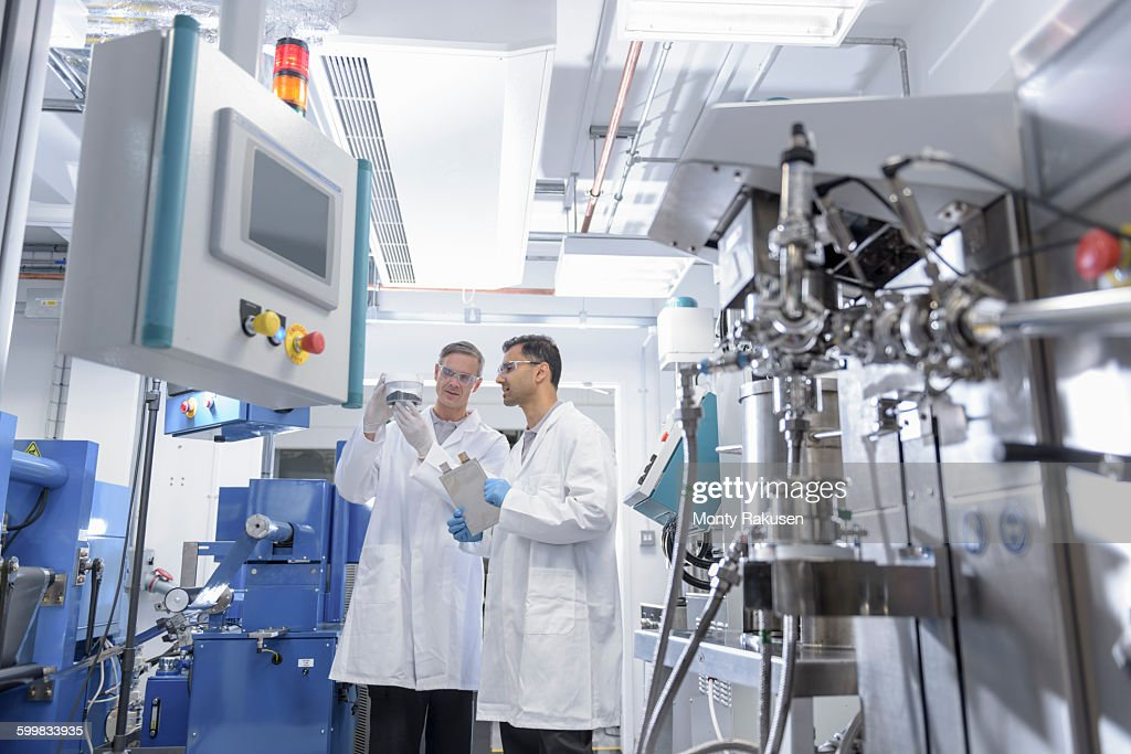 Scientists with lithium ion battery production line in battery research facility