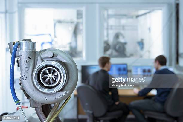 Scientists working at computers in turbo charger automotive research laboratory