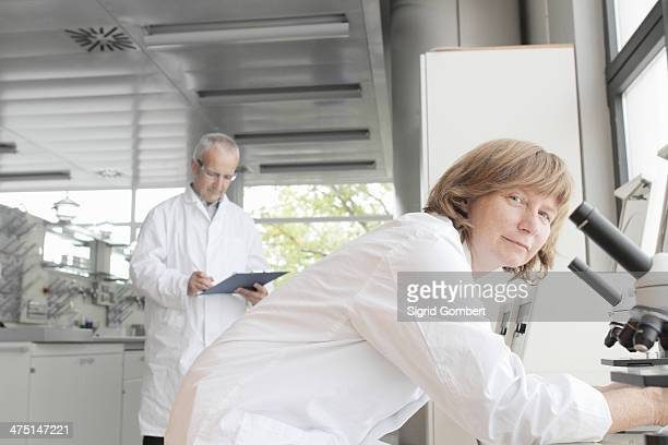 Scientists working in laboratory, woman with microscope and man taking notes