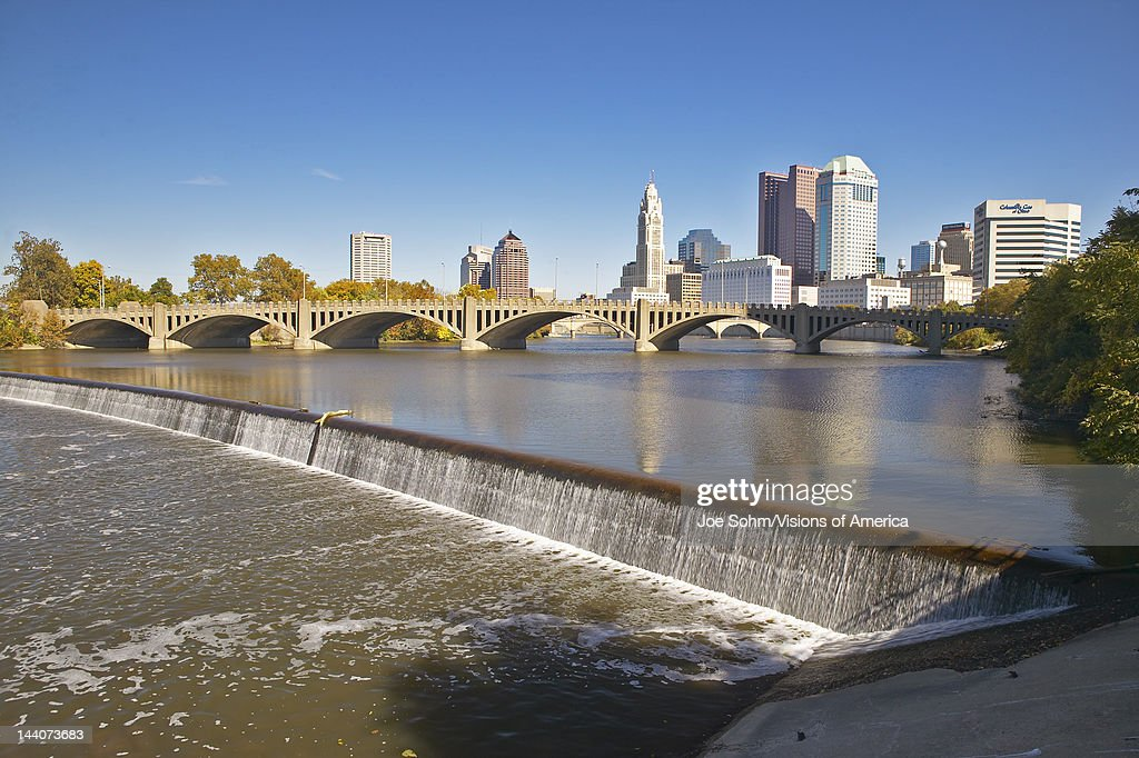 Scioto River with waterfall and Columbus Ohio skyline with setting sunlight
