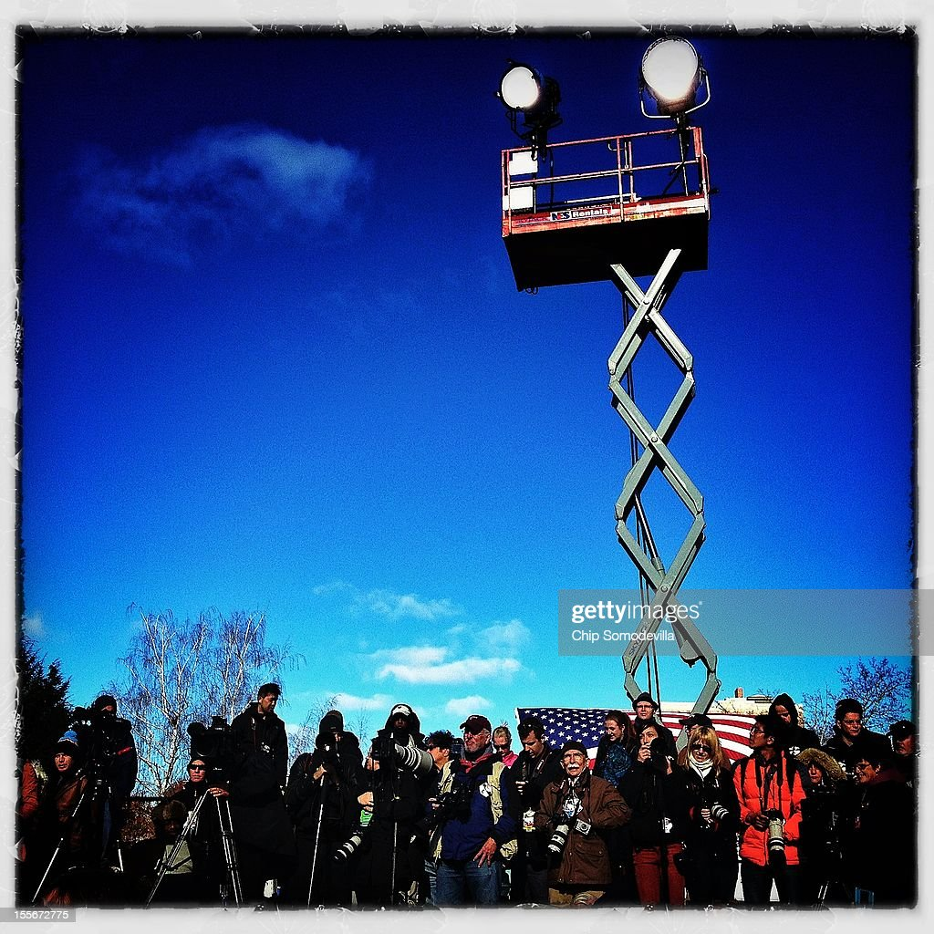 A scissor lift holds spotlights high above the heads of photojournalists standing on the 'cut shot' riser during a campaign rally with U.S. President Barack Obama in State Capitol Square November 4, 2012 in Concord, New Hampshire.