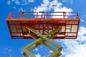 Scissor lift platform with hydraulic system at maximum height range painted in orange and beige colors, large construction machine, heavy industry, white clouds and blue sky on background