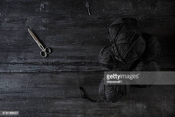 Scissors and balls of black wool on black wood