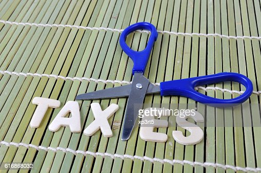 Scissors and the alphabet TAXES on bamboo rolling mat : Stock Photo