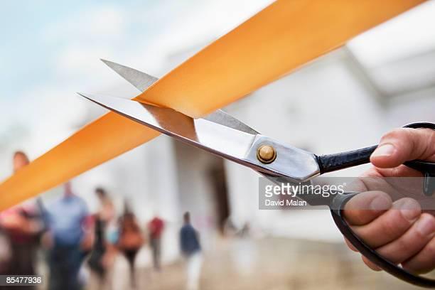 Scissors cutting ribbon, building in background