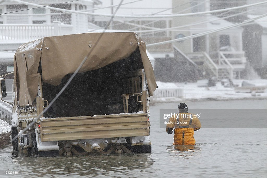 Scituate firefighter Danny Mendes wades in the water on Turner Road in Scituate.