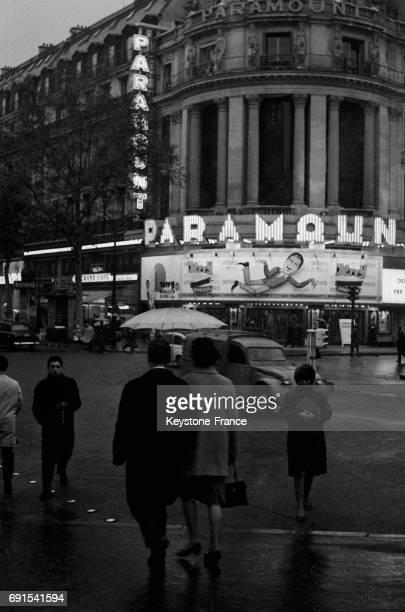 Scène de rue à Paris France avec un cinéma Paramount en arrièreplan le 3 novembre 1964