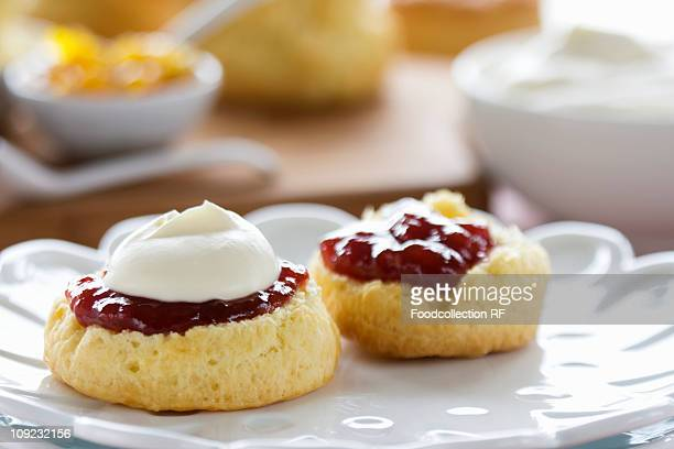 Scones with cream and jam on plate, close-up