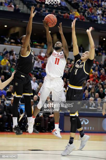 Scoochie Smith of the Dayton Flyers shoots the ball against Rashard Kelly and Landry Shamet of the Wichita State Shockers in the first half during...