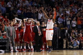 Scoop Jardine of the Syracuse Orange celebrates in front of the Wisconsin Badgers bench after winning their 2012 NCAA Men's Basketball East Regional...