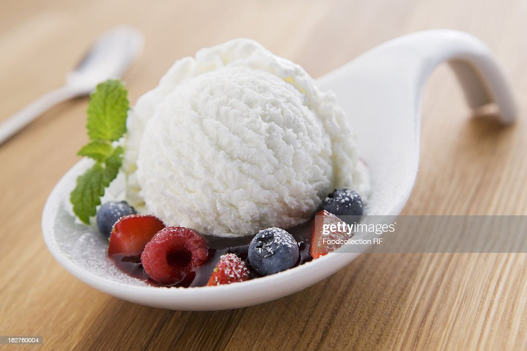 Scoop of yoghurt ice cream on spoon with berries : Stock Photo