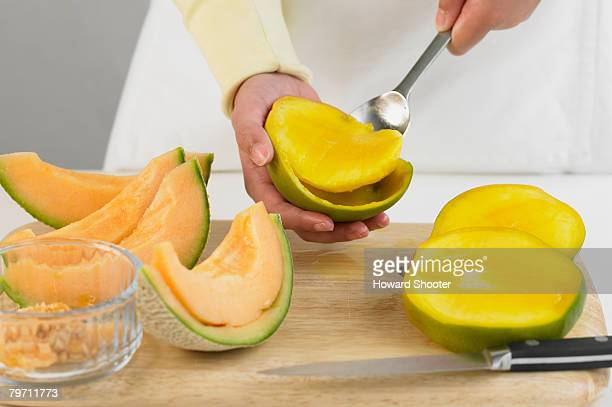 Scooping out the flesh of a mango, close up