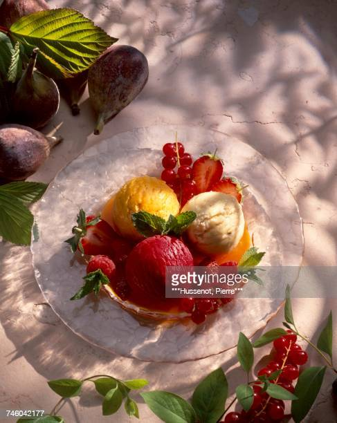 scoops of ice cream on bed of summer fruit