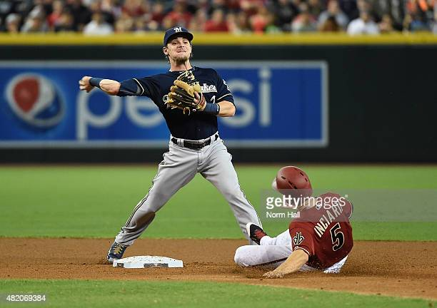 Scooter Gannett of the Milwaukee Brewers turns a double play as Ender Inciarte of the Arizona Diamondbacks slides into second base during the first...