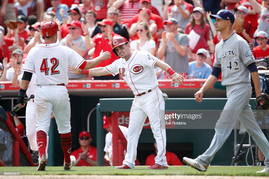 Scooter Gennett #4 and Zack Cozart #2 of the Cincinnati Reds celebrate after scoring runs following a double to left field by Jesse Winker in the sixth inning against the Milwaukee Brewers at Great American Ball Park on April 15, 2017 in Cincinnati, Ohio. The Reds defeated the Brewers 7-5. All players are wearing #42 in honor of Jackie Robinson Day.