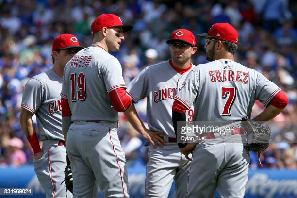 Scooter Gennett Joey Votto Jose Peraza and Eugenio Suarez of the Cincinnati Reds meet during a pitching change in the fourth inning against the...