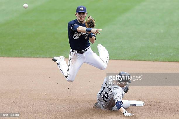 Scooter Gennett of t3he Milwaukee Brewers attempts a double play in the seventh inning sa Clint Barmes of the San Diego Padres slides into second...