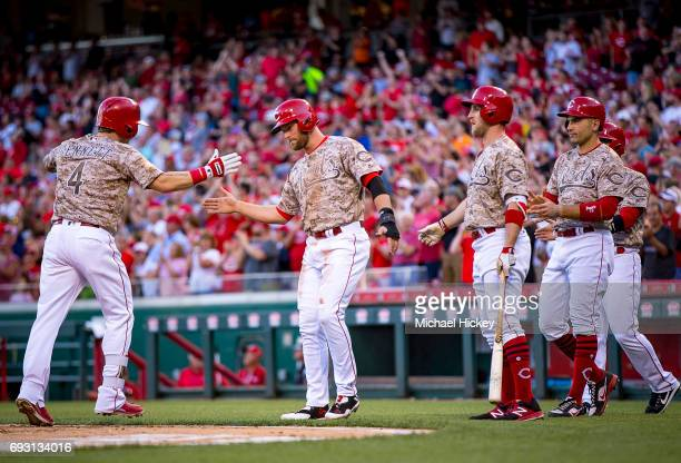 Scooter Gennett of the Cincinnati Reds is congratulated by teammates after hitting a grand slam in the bottom of the third against the St Louis...