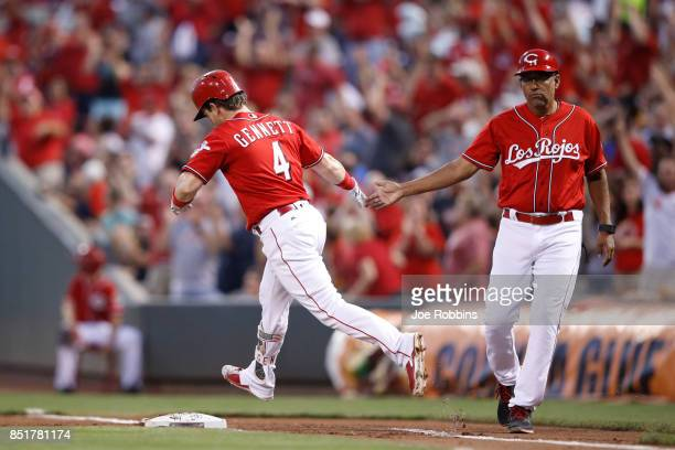 Scooter Gennett of the Cincinnati Reds rounds the bases after hitting a grand slam home run in the first inning of a game against the Boston Red Sox...