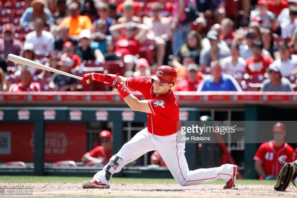 Scooter Gennett of the Cincinnati Reds singles to right field to drive in a run in the fifth inning of a game against the Miami Marlins at Great...