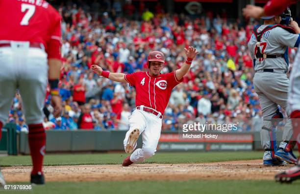 Scooter Gennett of the Cincinnati Reds slides into home after a three run double in the sixth inning against the Chicago Cubs at Great American Ball...