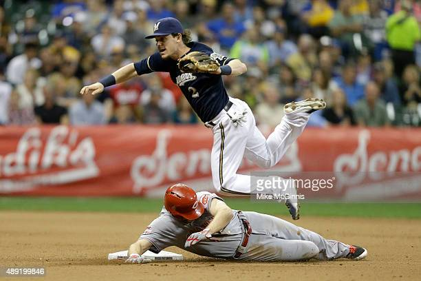 Scooter Gennett of the Milwaukee Brewers jumps over Brennan Boesch of the Cincinnati Reds while attempting a double play during the fifth inning at...