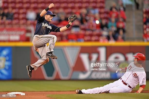 Scooter Gennett of the Milwaukee Brewers leaps to catch a high throw as Todd Frazier of the Cincinnati Reds steals second base in the fourth inning...