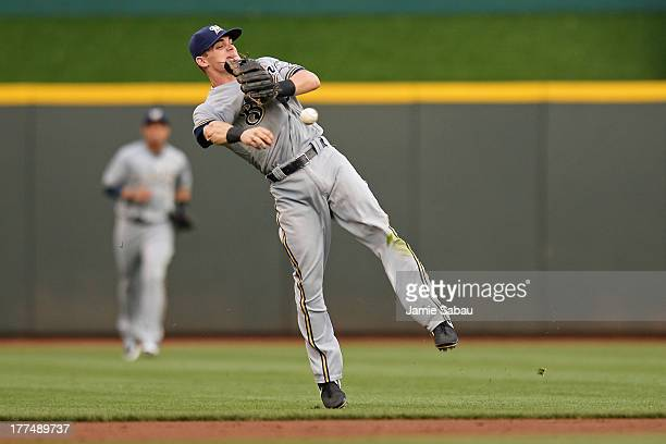 Scooter Gennett of the Milwaukee Brewers makes an offbalance throw to first base in the first inning at Great American Ball Park on August 23 2013 in...