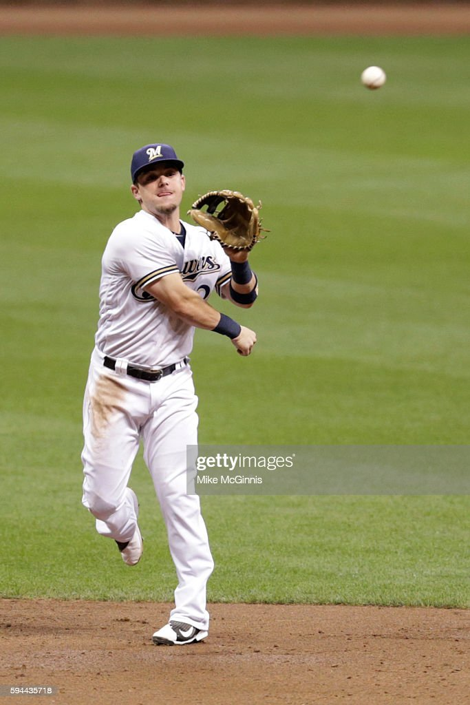 Scooter Gennett of the Milwaukee Brewers makes the throw to first base to retire Ryan Raburn during the third inning against the Colorado Rockies at...