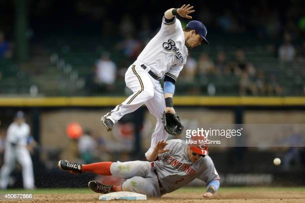 Scooter Gennett of the Milwaukee Brewers misses the grab from a wild throw from Jean Segura allowing Zack Cozart of the Cincinnati Reds second base...