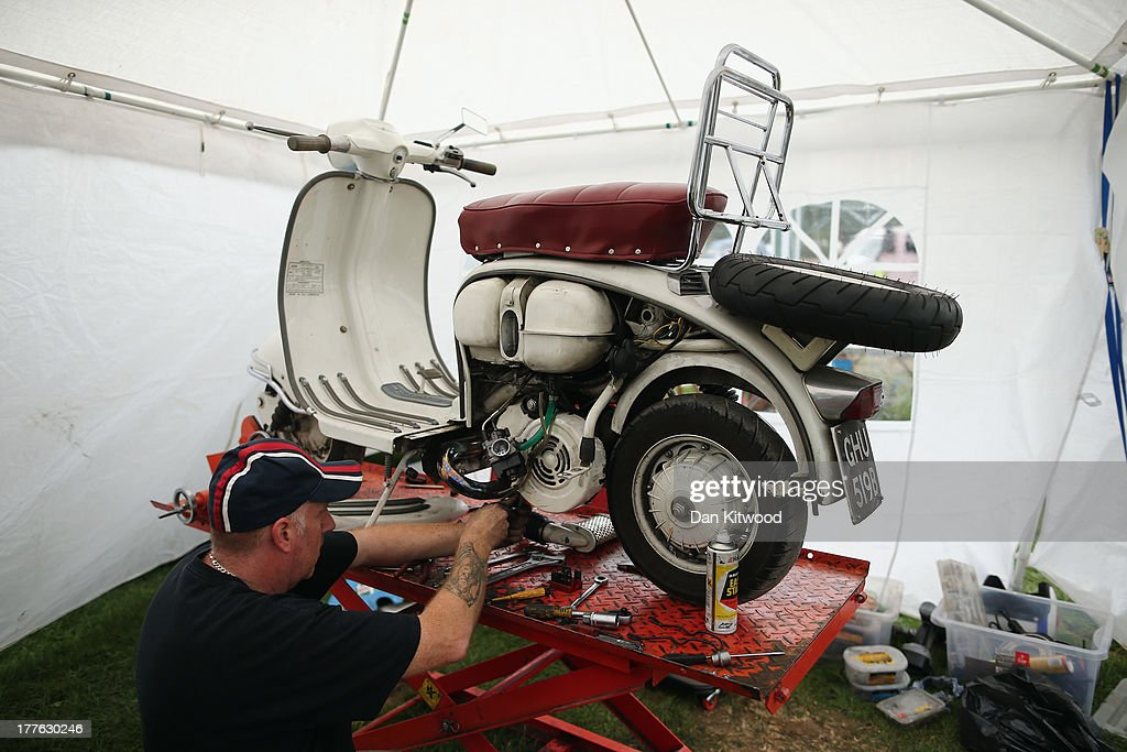 A scooter gets some mechanical repairs during the the Isle of Wight International Scooter Rally on the Esplanade on August 24, 2013 in Ryde, England. The annual event, which is organized by the British Scooter Rally Association and The VFM Scooter Collective, attracts around 6000 riders each year and has been running since 1980. The scooter in 1960's Britain was a fashion statement and the often heavily customized bikes, usually an Italian Vespa or Lambretta, became synonymous with the Mod scene. They provided an inexpensive mode of transport and escapism to an upwardly mobile youth at a time when public transportation stopped early. The Vespa was depicted on the cover of 'The Who's Quadrophenia album in 1973.